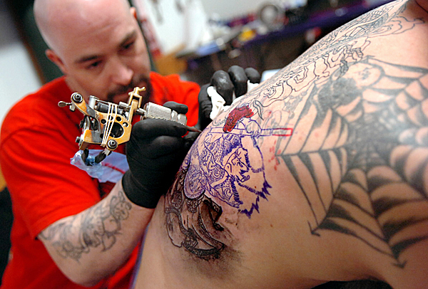 &quotI'm his sketchpad,&quot John Merchant of Rumford said of Christorpher O'Leary as O'Leary tattoos a Japanese woodblockpstyle design of samueai Miyamoto Musashi on Merchant's back at the Down East Tattoo Show at the Bangor Elks Club on Saturday.  BANGOR DAILY NEWS FILE PHOTO BY BRIDGET BROWN