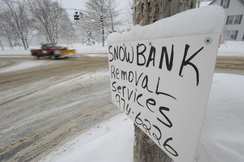 A sign advertising snow removal adorns a telephone pole at the corner of Stillwater Avenue and Broadway in Bangor on Wednesday, Jan.20, 1020. Area schools were canceled and traffic slowed around town as residents dug out from Tuesday night's snow storm. (Bangor Daily News/Kevin Bennett)