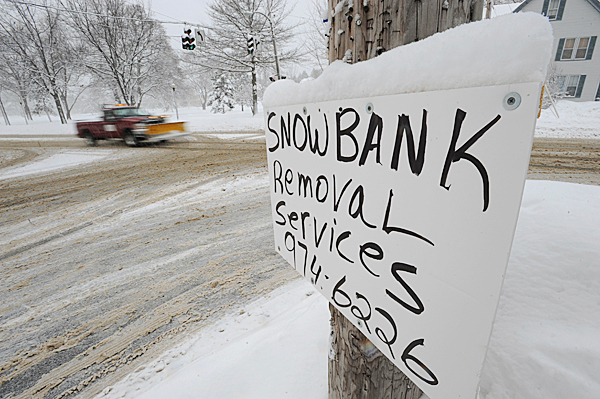 A sign advertising snow removal adorns a telephone pole at the corner of Stillwater Avenue and Broadway in Bangor on Wednesday, Jan.20, 1020. Area schools were canceled and traffic slowed around town as residents dug out from Tuesday night's snow storm. BANGOR DAILY NEWS PHOTO BY KEVIN BENNETT