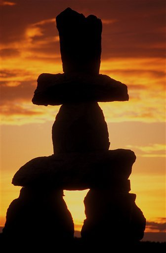 This photo released by Tourism British Columbia a silhouette of an Inukshuk rock sculpture at sunset in English Bay, Vancouver. (AP Photo/Tourism British Columbia,Tom Ryan)**NO SALES**