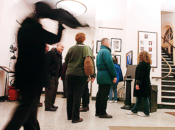 People look at artwork displayed at Bangor City Hall as part of the &quotBangor, Brush with History&quot exhibit, which featured work from 75 Maine artists at five different venues in honor of the city's 175th birthday Thursday, Jan. 14, 2010. One noticeable trend downtown in the last decade is that the sidewalks don't roll up at 5 p.m. and there are multiple events and venues to visit at night including art walks, which have been scheduled regularly since 2008. (Bangor Daily News/Bridget Brown)
