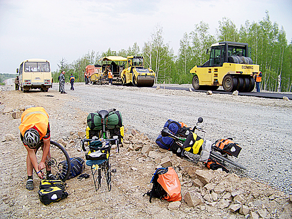 Broke Down: Rough rocks in a construction zone can easily pop tires. Ellery Althaus (pictured above) changes a flat. Dealing with constant bike problems and logistical challenges can quickly make a cyclist on a long tour admit it is the hardest thing they have ever done.  LEVI BRIDGES PHOTO