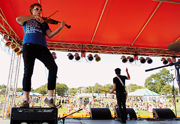 Evan James (left) of Orono, viola player and vocalist for the central Maine punk-pop band The Bay State, jams out on hsi viola as guitarist Tom Tash (right) of Lincoln thanks the crowd at the KahBang Music and Arts Festival on the Bangor Waterfront on Saturday.  (BANGOR DAILY NEWS PHOTO BY JOHN CLARKE RUSS)