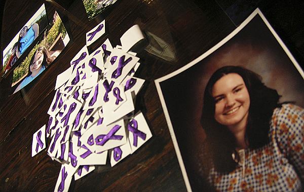Pictures of Katie Cabana are displayed next to a pile of purple domestic violence awareness ribbons at the University of Maine at Machias' Performing Arts Center on Saturday. Cabana and her friend, Aaron Settipani, were murdered two years ago by a former boyfriend of Cabana. A vigil was held Saturday to honor their memory and to raise awareness about domestic violence.  BANGOR DAILY NEWS PHOTO BY ERIC RUSSELL