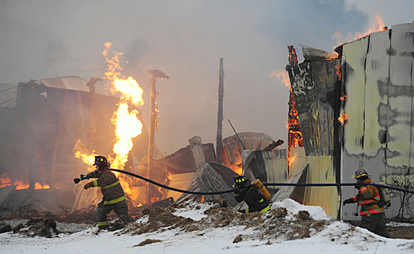 Firefighters move into position to cool off a flaring propane tank in the rear of Ireland's Auction and Retail on the Exeter Road in Corinna on Monday, Jan. 25, 2010. Fire crews from Corinna, Dexter, Corinth, St. Albans and Newport  assited in extinguishing the blaze. An employee who was in the building when it started around 1:15 p.m. made it out safely. The state fire marshall has been called in to investigate. BANGOR DAILY NEWS PHOTO BY KEVIN BENNETT