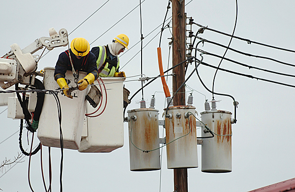 Bangor Hydro workers Mark Deschesne (left) and Dan Auxier work on replacing lines and service to the Cozy Inn and the New Stable Inn in Brewer on Tuesday, Jan. 26, 2010. A portion of the New Stable Inn's roof blew off in Monday's storm knocking down several lines with it and knocking out power to the Cozy Inn. BANGOR DAILY NEWS PHOTO BY BRIDGET BROWN