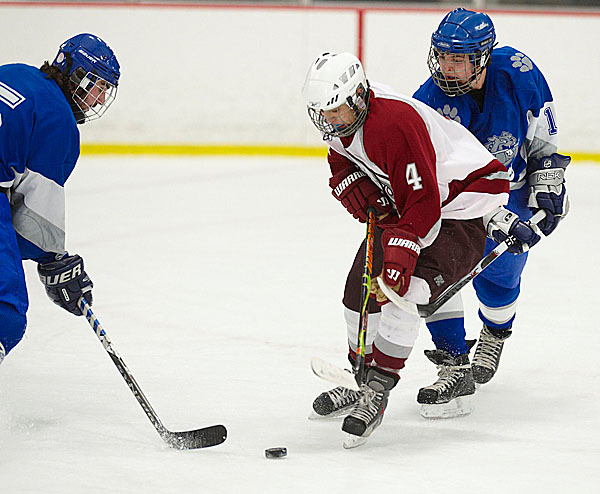 Lawrence's Jeshua Dearborn, (5), tries to pry the puck away from Bangor's Connor Griffin, (4), as Lawrence's Tyler Boudreau, (13), ties up his stick in the first period of their game in Bangor, Wed., Jan. 27, 2010. BANGOR DAILY NEWS PHOTO BY BRIDGET BROWN