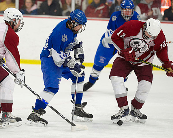 Bangor's Nate Lewis, (12), kicks the puck ahead as teammate Ryan King, (6), blocks the stick of Lawrence's Robert Banks, (18), in Bangor's offensive zone in the first period of their game in Bangor, Wed., Jan. 27, 2010. BANGOR DAILY NEWS PHOTO BY MICHAEL C. YORK