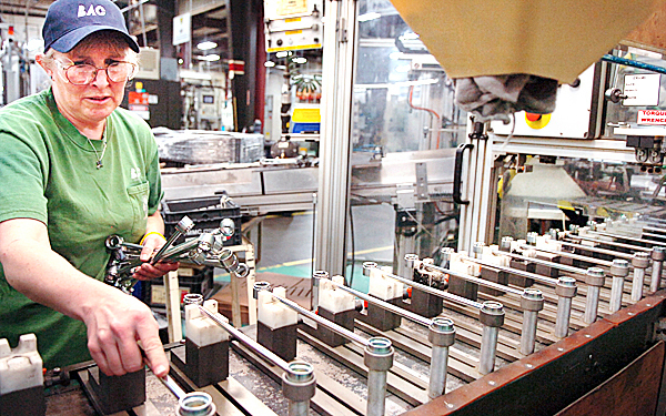 Tammy Robertson, who has been an employee at Brewer Automotive components for 10 years, loads stabilizer links for Toyota Corollas onto a machine to be modified and then shipped to an assembly plant on Thursday. BAC was founded in 1989 and is the sole supplier of steering and suspension components for Toyota in North America. The company has recently partnered with Eastern Maine Community College to offer continuing education and a chance for its employees to work twoard an associate of applied science degree.  (BANGOR DAILY NEWS PHOTO BY BRIDGET BROWN)