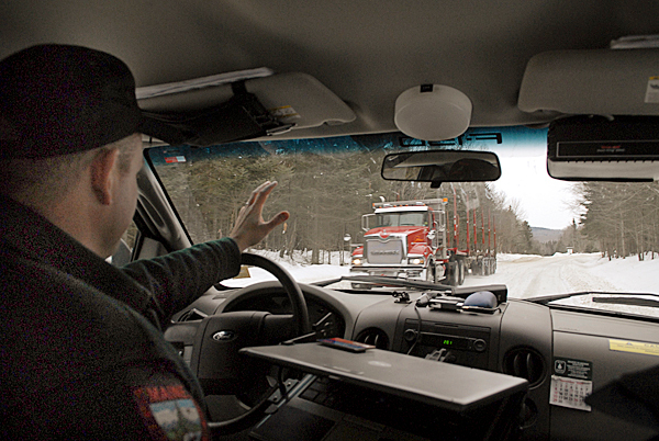 Sgt. Chris Cloutier of the Dept. of Inland Fisheries and Wildlife's Greenville regional office,  waves to a passing logging truck as he and the BDN reporters return to Greenville via the CO 490 Road from the  soon-to-be finished camp lodging on Baker Lake in located in T7 R17 WELS. Cloutier gave the BDN a tour of the lodging on December 28, 2009. BANGOR DAILY NEWS PHOTO BY JOHN CLARKE RUSS
