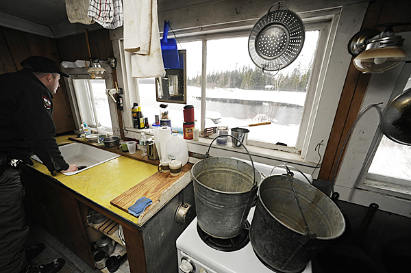 D.I.F.W. Sgt. Chris Cloutier peers out the window of the soon-to-be-razed camp house which overlooks Baker Lake and the Baker Branch of the St. John River. On the gas stove are buckets for heating water. The old structure is next to the the Dept. of Inland Fisheries and Wildlife's soon-to-be-finished new camp lodging on Baker Lake in located in T7 R17 WELS. Cloutier gave the BDN a tour of the old and new lodging on December 28, 2009. BANGOR DAILY NEWS PHOTO BY JOHN CLARKE RUSS