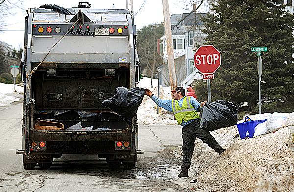 Steve Davis, an employee of Pine Tree Waste of Hermon, throws trash bags into a garbage truck in Bangor on Thursday, Jan. 28, 2010. The City of Bangor is considering a pay-as-you-throw trash collection program that would require Bangor residents to purchase trash bags from the city that would be collected curbside. BANGOR DAILY NEWS PHOTO BY KEVIN BENNETT