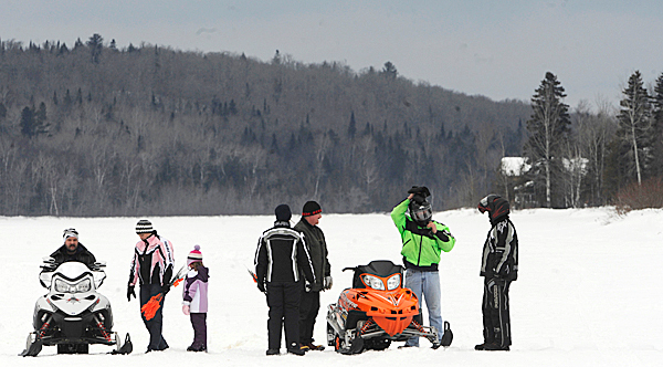 On Saturday, January 16, 2010 members of the Portage Lakers Snowmobile Club stop to confer while getting their ice track ready to their ninth annual snowmobile Radar Runs the next day on Portage Lake. Snowmobiling brings approximately $300 million to $350 million annually to the state's economy. BANGOR DAILY NEWS PHOTO BY JOHN CLARKE RUSS