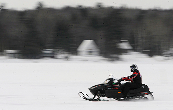 A snowmobile enthusiast blurs by on Portage Lake Saturday morning, January 16, 2010. Snowmobiling brings approximately $300 million to $350 million annually to the state's economy. BANGOR DAILY NEWS PHOTO BY JOHN CLARKE RUSS