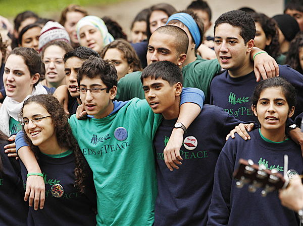 Seeds of Peace campers from several countries sing the camp song at a flag-raising ceremony, Wednesday in Otisfield. The camp has been bringing together young people from countries at conflict for 17 summers in hopes of moving them beyond deep-rooted hatreds.  AP PHOTO BY ROBERT BUKATY