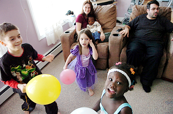 Leftover balloons from a welcome home party make for endless entertainment at the Logiodice home in Pittsfield for Donovan, 8, (left) Bella, 4, (center) and Christella, 5, under the watchful eye of their parents Amanda and Jediah on Friday, Jan. 29, 2010.  BANGOR DAILY NEWS PHOTO BY BRIDGET BROWN