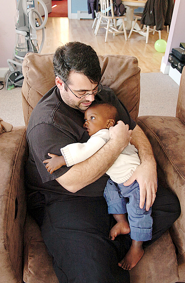 &quotHe needs all the hugs in the world,&quot Amanda Logiodice (not pictured) said of her son Jediah who is held by his father, also Jediah Logiodice on Friday, Jan. 29, 2010 at their Pittsfield home. Jediah and Christella were adopted from an orphanage in Port-au-Prince, Haiti that was destroyed in the massive earthquake earlier this month.   BANGOR DAILY NEWS PHOTO BY BRIDGET BROWN