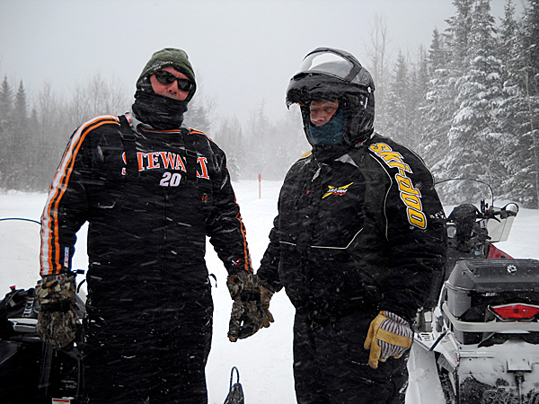 Meeting friends along the trail is all part of snowmobiling in northern Maine. Gary Pelletier, right, takes a moment to talk conditions over with Jerry Beaulieu who was on his way to open up a section of trail around Square Lake following Friday's snowfall. PHOTO BY JULIA BAYLY