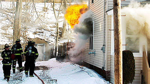 Firefighters wait for hoses to be charged with water as flames lick up the side of Bruce Babin's home at 92 Second Street in Bangor on Thursday afternoon, Feb. 4, 2010.    BANGOR DAILY NEWS PHOTO BY KEVIN BENNETT
