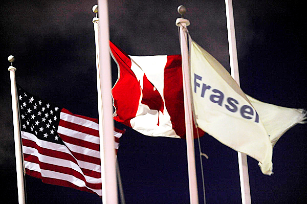 The U.S. and Canadian Flag fly next to Fraser Paper's flag at the Fraser Paper mill in Madawaska--- less than 50 yards from the border crossing into Canada. Photogrpahed Thursday evening, February 4, 2010. BANGOR DAILY NEWS PHOTO BY JOHN CLARKE RUSS