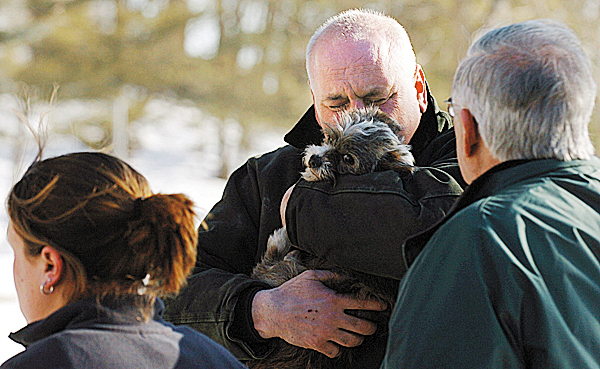 Homeowner Bruce Babin, center, hugs his dog, Seamus after firefighters rescued the canine from the second floor of Babin's home at 92 Second Street in Bangor on Thursday. Feb. 4, 2010. The home suffered heavy fire damage in a rear extension and smoke damage thoughout the rest of the house.   BANGOR DAILY NEWS PHOTO BY KEVIN BENNETT