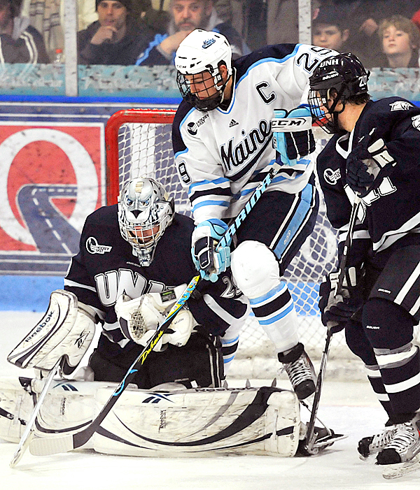 Maine's Tanner House, (29), tries to pry a loose puck as UNH goalie Brian Foster, (29), holds on in the second period of their NCAA hockey game in Orono, Maine, Friday, Feb. 5, 2010.  BANGOR DAILY NEWS PHOTO BY MICHAEL C. YORK