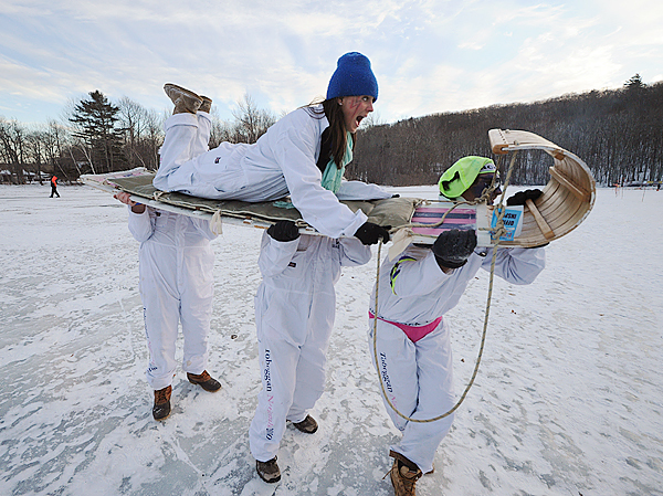 Kristin Phelps gets a ride from fellow Wack Jill team members, Alden Hawkins, left, Josh Gothard, center, and Brian Mahoney after the foursome made one of their runs at the 20th Annual National Toboggan Championships at the Camden Snow Bowl on Saturday, Feb. 5, 2010. BANGOR DAILY NEWS PHOTO BY KEVIN BENNETT