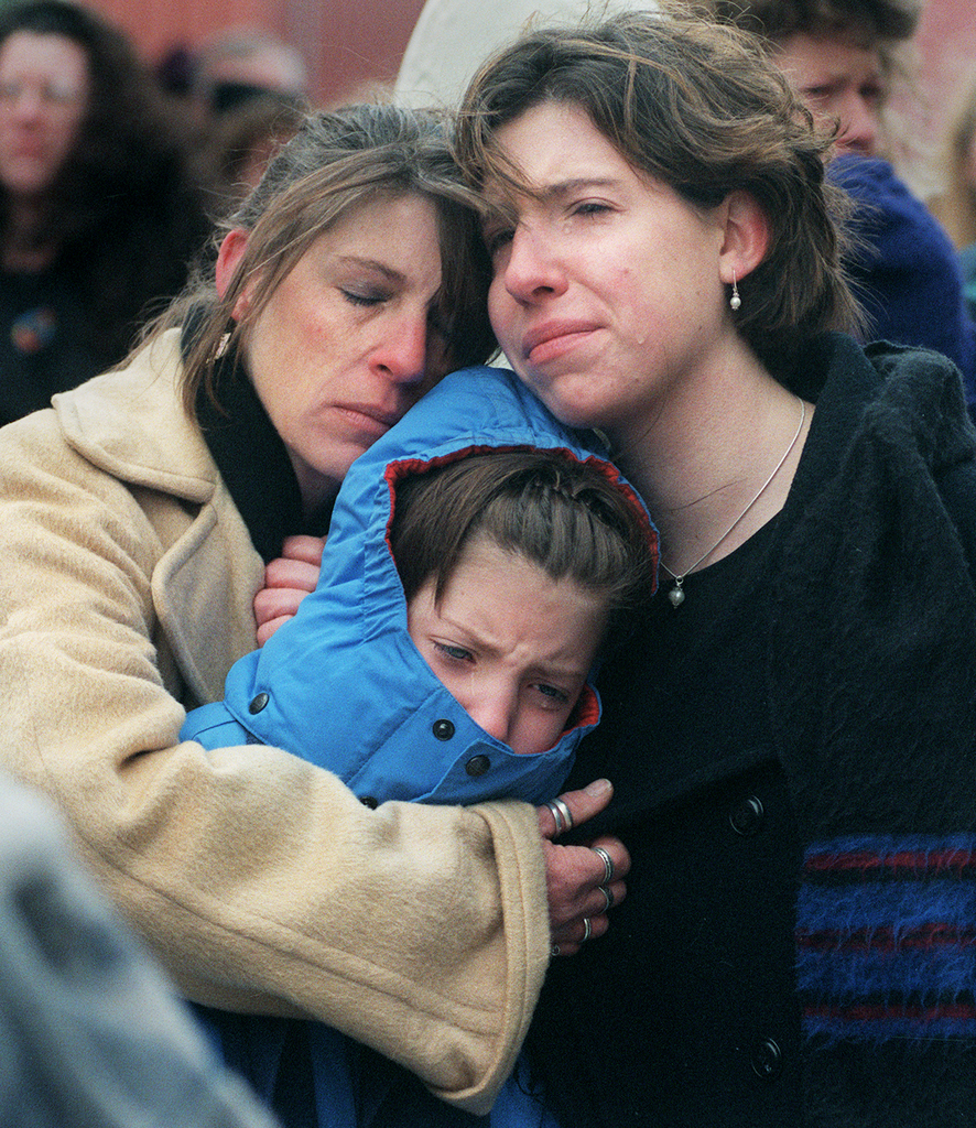 Robin Trudeau (left) of Brooks holds her daughters Elizabeth (center) and Megan at Unity Station during the memorial service in 2000 for the White triplets who died in a fire 10 years ago.
