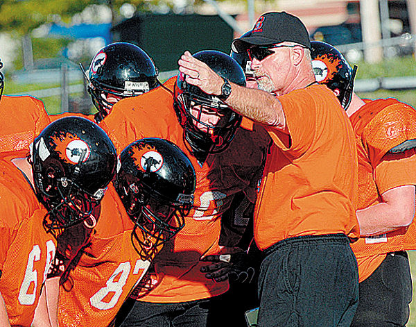 Brewer assistant football coach Dana Corey (right) talks with his players during a pre-season practice in late August.  (BANGOR DAILY NEWS PHOTO BY BOB DELONG)