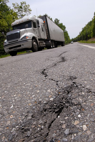 A truck passes a crack on Route 15 in Monson on Friday afternoon. Road conditions on Route 15 are so bad, Greenville officials say, that motorists have lost tailgates, tires and snowmobile trailers.  BANGOR DAILY NEWS FILE PHOTO BY JOHN CLARKE RUSS