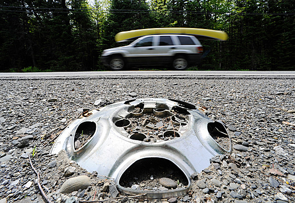 A hubcap is buried on the side of Route 15 in Monson as traffic passes Friday afternoon. Vehicle parts are starting to outnumber roadkill as many stretches of Route 15 in the Moosehead Lake region have fallen into disrepair. BANGOR DAILY NEWS FILE PHOTO BY JOHN CLARKE RUSS