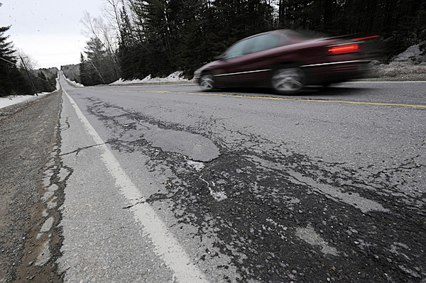 A car passes over cracked and bumpy pavement on Route 15 in Monson on Wednesday, Feb. 10, 2010. BANGOR DAILY NEWS PHOTO BY KEVIN BENNETT