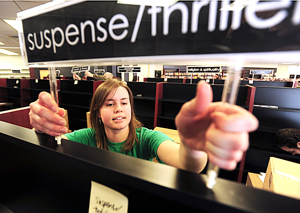 Bull Moose Music employee Lindsay Heald installs a sign on new book shelves as other employees open cases of books and categorize them on Wednesday, Feb. 10, 2010.   BANGOR DAILY NEWS PHOTO BY KEVIN BENNETT