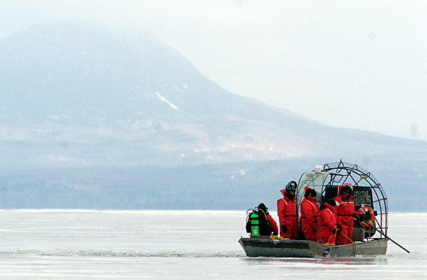 From their search and rescue boat, Maine Warden Service personnel keep an eye on one of their divers Friday morning near the East Outlet of Moosehead Lake. On Thursday three persons on shore said they spotted a person struggling in the water near the East Outlet behind Wilsons campground which promted game wardens and other emergency responders to the area. Two dives were conducted Friday morning and no evidence of a person or their belongings was found, according to game wardens.  BANGOR DAILY NEWS PHOTO BY JOHN CLARKE RUSS