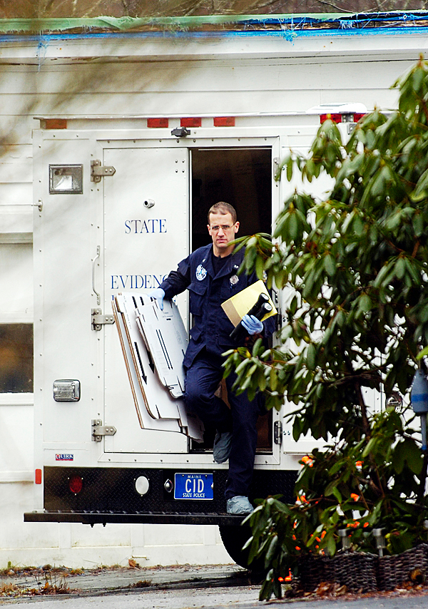Maine State Police Detective Bryant Jacques takes empty boxes into the hosue located at 346 High St. in Belfast on Wednesday. State police detectives say 29-year-old James Cummings was shot by his wife, 31-year-old Amber Cummings, a t their residence on Tuesday.  BANGOR DAILY NEWS FILE PHOTO BY KEVIN BENNETT