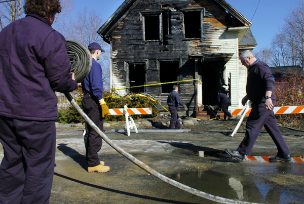 Members of the Orono Fire Department including Ben Pratt (left) and Paul Haley (right) work to clean up the scene of a fire at 34 Pine Street in Orono on Saturday, Feb. 13, 2010, which occured around 7 p.m. Friday and destroyed the house. Four residents, some of them University of Maine students, were displaced but apart from a cat that died, no one was injured in the fire. An investigation is underway to determine the cause of the blaze.  BANGOR DAILY NEWS PHOTO BY BRIDGET BROWN