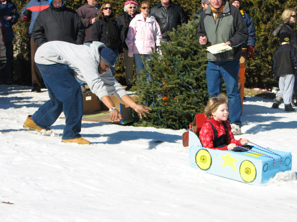 Alex Britt, 23, of Ellsworth pushes his sister, Kaitlyn Britt, 9, as she rides a homemade sled down the front lawn of Woodlawn Museum in Ellsworth on Saturday, Feb. 13, 2010. The cardboard sled event was part of the museum's day-long Fourth Annual Winter Carnival.  BANGOR DAILY NEWS PHOTO BY BILL TROTTER