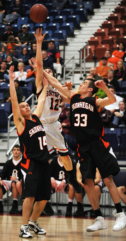 Brewer's Ray Bessette, center shoots over Skowhegan defenders, Lucas Fortier (14) and Josh Wescott (33) during Class A quarter final action on Saturday, Feb. 13, 2010 at the Augusta Civic Center. Brewer beat SKowhegan 63-53.  BANGOR DAILY NEWS PHOTO BY KEVIN BENNETT