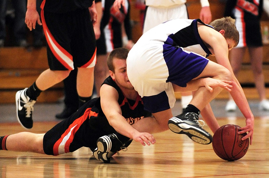 Brunswick's John Williams, left, collides with Hampden's Brad Dolan,right as the two scramble for a loose ball during 2nd period action on Saturday, Feb. 13, 2010 at the Augusta Civic Center during Class A quarter final action.