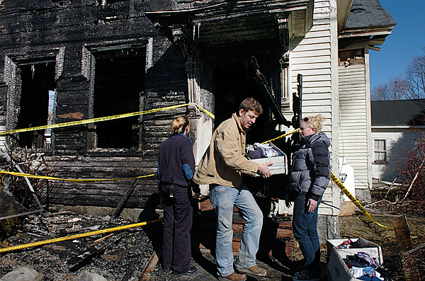 University of Maine senior Zach Knox (center) helps remove salvaged clothing from the house that fellow senior Tessa Black (right) shared with five others as Orono Fire Department Lt. Erin Frank (left) works to clean up the scene of a fire at 34 Pine Street in Orono on Saturday, Feb. 13, 2010, which occured around 7 p.m. Friday. No one was injured in the fire whose cause is still under investigation. BANGOR DAILY NEWS PHOTO BY BRIDGET BROWN