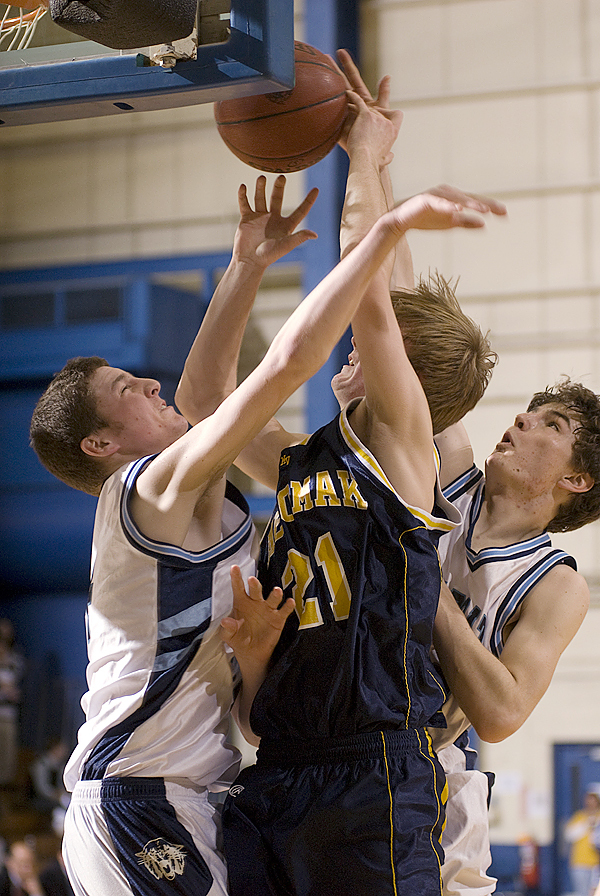 Medomak Valley's Isaac Greenrose is fouled by Presque Isle's Jason Hughes (right) as he and teammate Keenan Eaton block a shot in second half action of Saturday morning's  Class B tournament game at the Bangor Auditorium.  Medomak Valley won the game 46-42. BANGOR DAILY NEWS PHOTO BY LINDA COAN O'KRESIK
