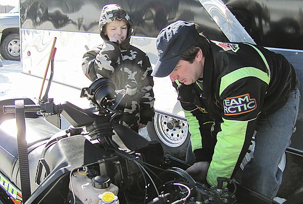 Spencer Dyer, 5, helps his father, Scott Dyer Jr., change a drive belt during Saturday's Wassookeag Snowmobile Club Radar Runs in Dexter. BANGOR DAILY NEWS PHOTO BY CHRISTOPHER COUSINS