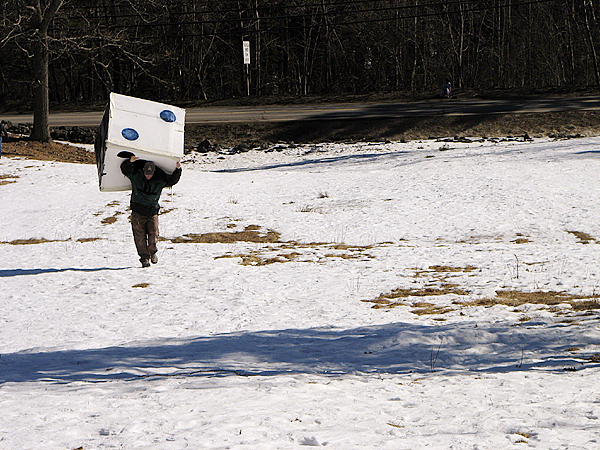Wayne Sawyer of Trenton carries a large box painted to look like a six-sided die up the sledding hill at Woodlawn Museum in Ellsworth on Saturday, Feb. 13, 2010. Sawyer's son and two other children had ridden inside the box as it slid down the hill during cardboard sled races that were held as part of the museum's day-long Fourth Annual Winter Carnival. BANGOR DAILY NEWS PHOTO BY BILL TROTTER