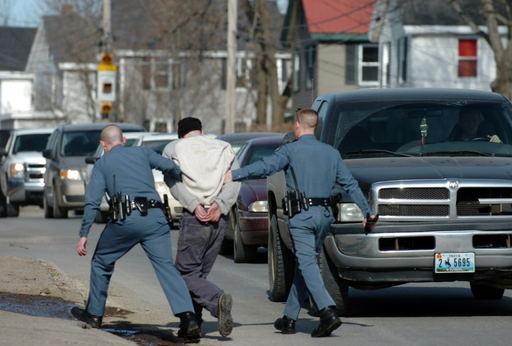 Maine State Police troopers walk Christopher Norris, 28, of Bangor across Broadway in Bangor after his arrest Tuesday morning, Feb. 16, 2010 near St. Joseph Hospital. According to Sgt. Sean Hashey, Norris was riding as a passenger in a car when the driver was stopped for a motor vehicle violation and Norris fled from the vehicle. Norris was arrested for outstanding warrants and will likely be charged with criminal threatening according to Hashey because &quothe claimed that he had a firearm and that he would shoot.&quot (Bangor Daily News/Bridget Brown)