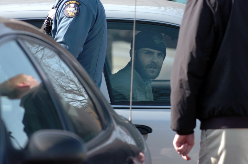 Christopher Norris, 28, of Bangor looks out from a patrol car after being arrested on Tuesday morning, Feb. 16, 2010 near St. Joseph Hospital in Bangor. According to Maine State Police Sgt. Sean Hashey, Norris was riding as a passenger in a car when the driver was stopped for a motor vehicle violation and Norris fled from the vehicle. Norris was arrested for outstanding warrants and will likely be charged with criminal threatening according to Hashey because &quothe claimed that he had a firearm and that he would shoot.&quot (Bangor Daily News/Bridget Brown)