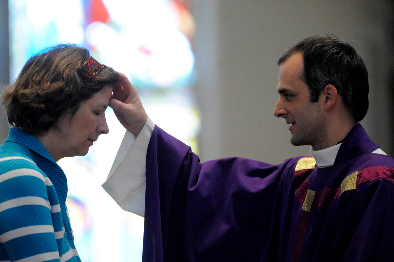 (BANGOR DAILY NEWS PHOTO BY JOHN CLARKE RUSS)  CAPTION  Parishioner Jennifer Ross of Holden has ash smudged on her forehead by the Rev. Seamus Griesbach during Ash Wednesday services at St. John?s Catholic Church. (Bangor Daily News/John Clarke Russ)