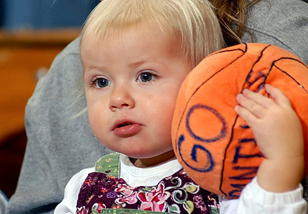 Sitting with her mother, one-year-old Sarah Haskell of Hampden, holds tight to her stuffed basketball while watching Medomak Valley and Camden Hills in the Class B boys semi final game on Wednesday at the Bangor Auditorium.  Sarah's cousin Jason Vinal is a senior guard for Medomak Valley. BANGOR DAILY NEWS PHOTO BY LINDA COAN O'KRESIK