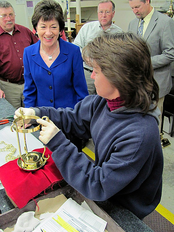 Toni Kirk of Canaan explains to Sen. Susan Collins, R-Maine, how she inspects and assembles some of the products manufactured by C.M. Almy in Pittsfield, such as this sanctuary candle holder. BANGOR DAILY NEWS PHOTO BY CHRISTOPHER COUSINS