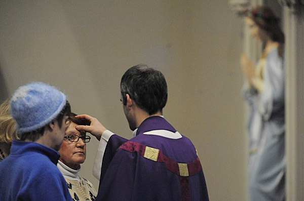 Nancy Long, a eucharistic minister and church administrator, has ash smudged on her forehead by the Rev. Seamus Griesbach during Ash Wednesday services Wednesday morning at St. John?s Catholic Church. Joining her were fellow eucharistic ministers  Kathy Percival (in blue), and Pat Judd (obscured). BANGOR DAILY NEWS PHOTO BY JOHN CLARKE RUSS
