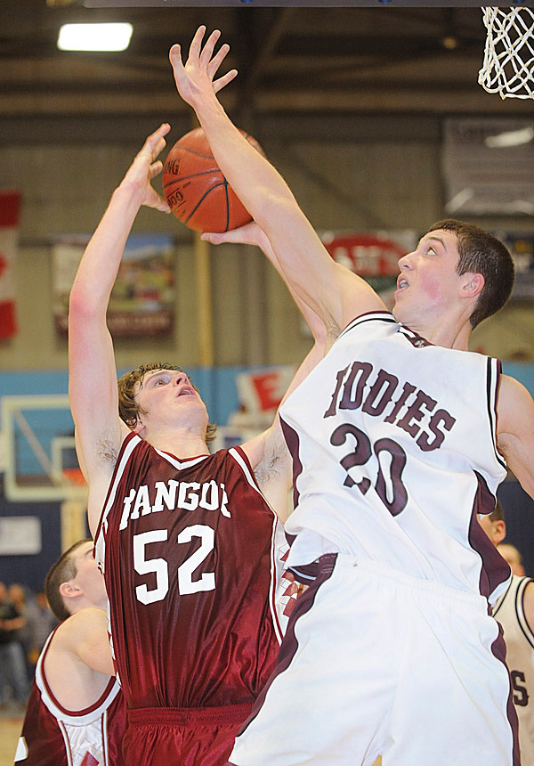 Edward Little's Bowen Leary (right) blocks a shot by Bangor's Clark Noonan during the second half of the Class A semifinal game in Augusta Wednesday.  bangor lost in overtime 60-57. BANGOR DAILY NEWS PHOTO BY GABOR DEGRE